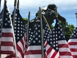 Flags surround soldier, cast in bronze, who storms the beach.