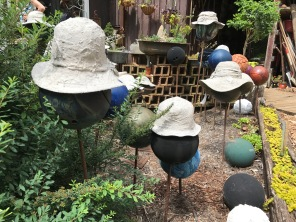 Cement encrusted hats rest on bowling ball hat stands